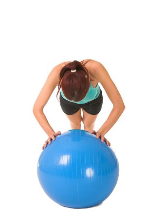 Woman in gym wear bending down on blue ball. photo
