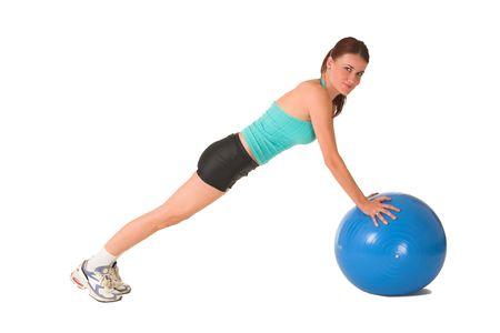 bending down: Mujer en el desgaste del gym que se dobla abajo en bola azul.