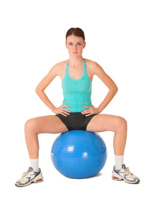 Woman sitting on gym ball with hands on her hips. photo