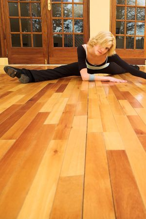 limber: A Female Dancer practicing in her studio - in a split, on the floor - Copy Space Stock Photo
