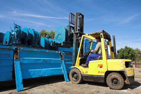 Yellow Forklift placing cargo on Flatbed truck for dispatch photo