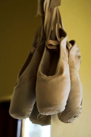 Pair of Ballet shoes hanging on the wall against a mirror – Shallow Depth of Field photo