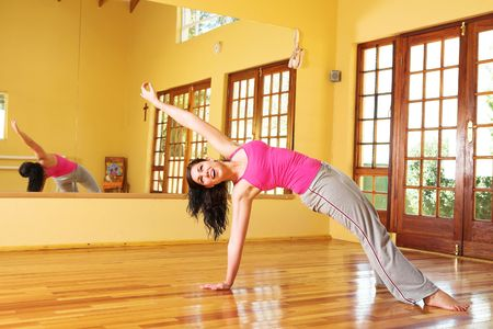 Healthy young woman with dark hair exercising in studio. Yoga stretches associated with health and wellness, as well as general fitness and dieting. Stock Photo