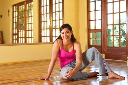 associated: Healthy young smiling woman with dark hair sitting on the wooden floor in her exercise studio. Resting after yoga stretches associated with health and wellness, as well as general fitness and dieting.