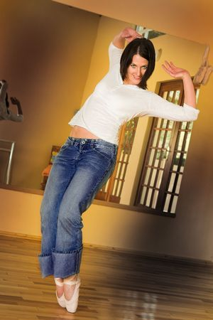 Modern Ballet Dancer in blue jeans and Pointe Shoes. Practicing in Studio photo