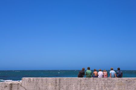 breakwater: Seven friends sitting together on the harbor breakwater wall Stock Photo