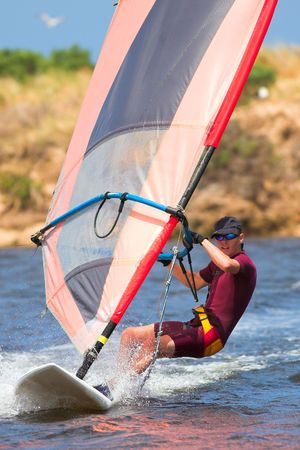 Fast moving windsurfer on the water at Keurbooms Lagoon, South Africa � Movement on windsurfer extremities Stock Photo