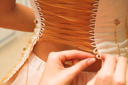 vistiendose: Novia vestirse, Bare back - Ribbon est� roscado. Enfoque en el Cintas  Foto de archivo