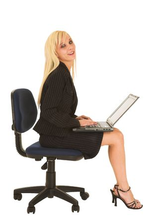 Blond business woman in black dress business suit, sitting down, with notebook computer on her lap photo