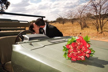 Red bouquet of roses on the bonnet of a car, just married bridal couple kissing in the background. Focus on Flowers photo