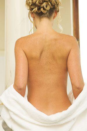 freckle: Woman undressing in a bathroom, bathrobe over buttocks