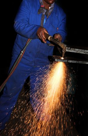 Worker in Blue safety overalls working with Plasma cutter - Focus on sparks photo