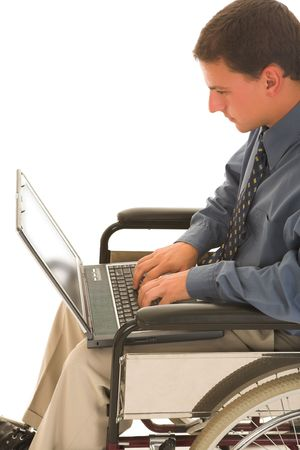Man sitting in a wheelchair working on a laptop.