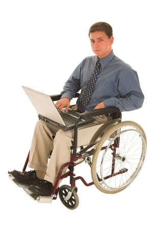 Businessman sitting in a wheelchair working on laptop photo