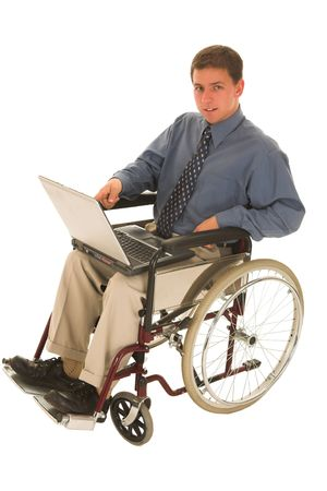 Businessman sitting in a wheelchair working on laptop