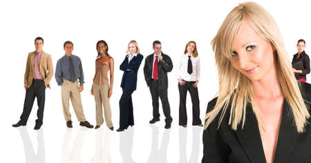 Beautiful blonde businesswoman standing in front of a group of business people all isolated on white. The whole group consists of multiracial young adults. The foreground is in sharp focus with the people in the background slightly blurred.