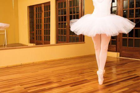 Lady doing ballet in dance studio.