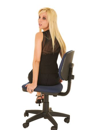pencil skirt: A young blonde businesswoman in a formal black pinstripe suite with pencil skirt, sitting on an office chair - isolated on a white background Stock Photo