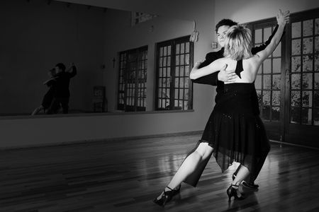 A young adult couple dancing and practicing ballroom dancing together in a studio - Focus on man, black and white image