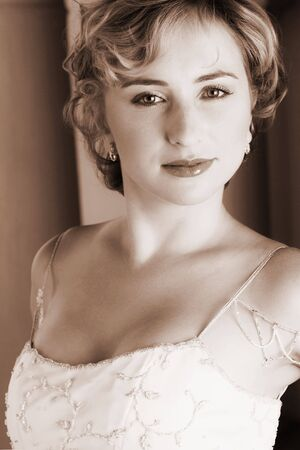 Young blonde bride with champagne colored wedding gown and red lips. She is looking over her shoulder with an alluring and seductive look in her green eyes. She is in a luxurious bedroom - Duatone brown image (sepia tone) photo