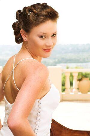 rote lippen: Junge sch�ne brunette Braut mit Champagner f�rbte Hochzeit Kleid und rote Lippen. Sie schaut �ber ihrer Schulter mit einem anziehenden und seductive Blick in ihren gr�nen Augen. Sie ist drau�en an einem sonnigen Tag