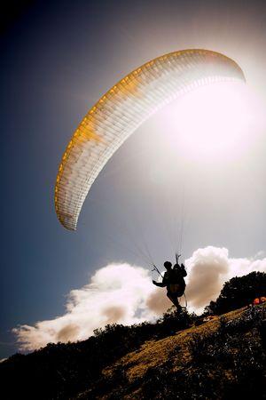 parapente: Paraglider lancering van de kam met een gele en witte kap en de zon van achter. De paraglider is een silhouet en het schot wordt genomen direct na het opstijgen. De paraglider is scherp, met een lichte beweging op de vleugel Stockfoto