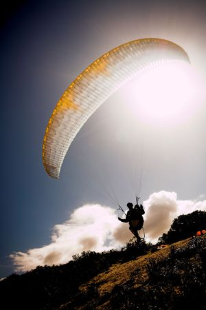 Paraglider launching from the ridge with a yellow and white canopy and the sun from behind. The paraglider is a silhouette and the shot is taken right after takeoff. The paraglider is sharp, with slight movement on the wing Stock Photo
