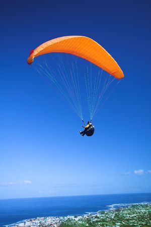 paraglide: Paraglider launching from the ridge with an orange canopy and the sun from behind. The paraglider is standing out against the blue sky and the shot is taken right after takeoff. The paraglider and pilot is both sharp Stock Photo