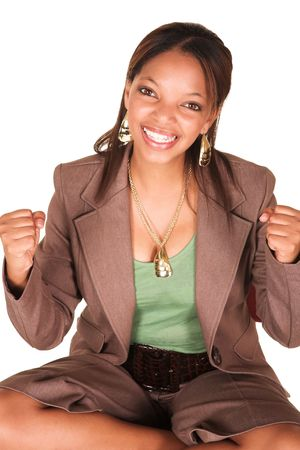 short sleeved: A short smiling African businesswoman with brown trousers and a short sleeved green top and a faux leather belt. She has both arms in fists and is smiling at the viewer. Isolated on white. Stock Photo