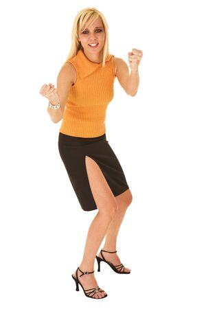Blond businesswoman in small black dress and orange top isolated on white standing with her fists in the air. Slightly frustrated, but still smiling photo