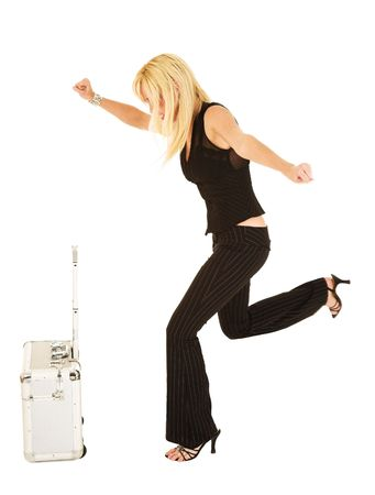Blonde frustrated businesswoman in black trousers kicking luggage - isolated on white - movement on back foot