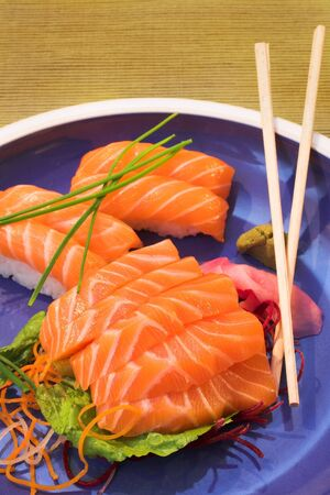Fresh strips of Norwegian salmon Nigiri and rice Sashimi on a blue plate with a bamboo mat in the background and wooden chopsticks on the plate Stock Photo