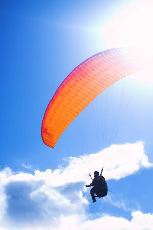 paraglide: Paraglider launching from a ridge with an orange canopy and the sun from behind. The paraglider is a silhouette and the shot is taken right after takeoff. The paraglider unfocused with movement, with the main focus on the canopy Stock Photo