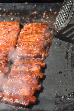Succulent and saucy de-boned pork ribs on a gas powered, Teflon coated barbeque set. The meat is almost ready and is being checked with a black plastic spatula. Shallow Depth of Field with the selective focus on the back part of the front ribs photo