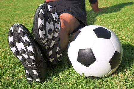 togs: A male soccer (football) player, referee or coach sitting next to a soccer ball. The image is of feet and legs, with soccer togs, and a black and white ball. Focus on soccer ball and heels