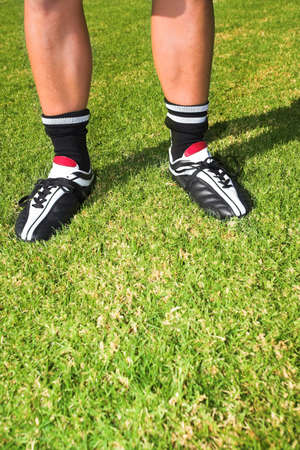 togs: A male soccer (football) player, referee or coach standing on a soccer pitch. The image is of feet and legs, with soccer togs. copy space on de-focused grass Stock Photo