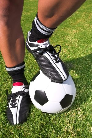 togs: A male soccer (football) player, referee or coach standing with one foot on a soccer ball. The image is of feet and legs, with soccer togs, and a black and white ball
