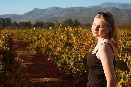 closed eyes: Mooie blonde vrouw met gesloten ogen in de ondergaande zon in het najaar een wijngaard op Boschendal, Western Cape, Zuid-Afrika. Ondiepe scherptediepte. Focus op alleenstaande vrouw Stockfoto