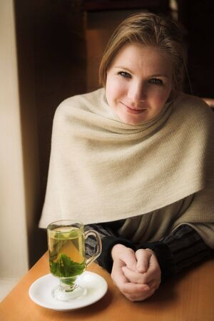 field mint: Blonde woman with hot mint tea next to a natural light window in the beginning of winter. Shallow Depth of Field Stock Photo