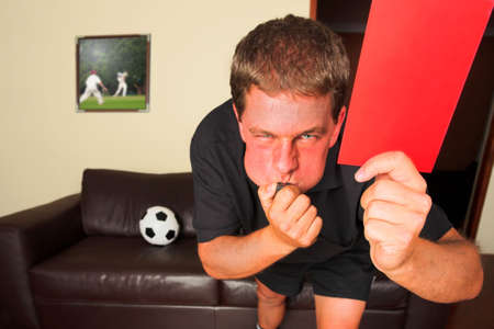 A typical sports fan as a referee in his sitting room, blowing a whistle and showing a red card or penalty card to send off an offending player. Cricketers on image in background by same artist. Soccer ball on the leather couch. Shallow DOF, Focus on hand Stock Photo