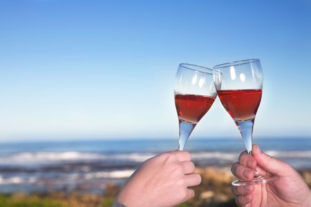 Couple toasting wineglasses next to the ocean against a blue sky on a summers day Stock Photo