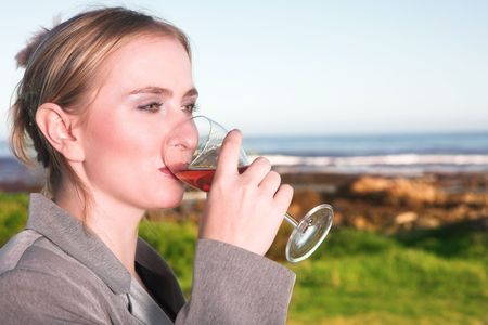 Young blonde Caucasian woman drinking wine next to the ocean wearing a business suit Stock Photo - 960753