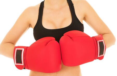 Sexy young adult woman in black gym outfit isolated on white. She is wearing large red boxing gloves