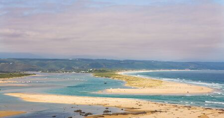 inlet bay: A cloudy day at the Keurbooms Lagoon next to Plettenberg Bay. Clean golden beaches with people sunbathing on the sand and boats in the water. The new river mouth visible. Stock Photo