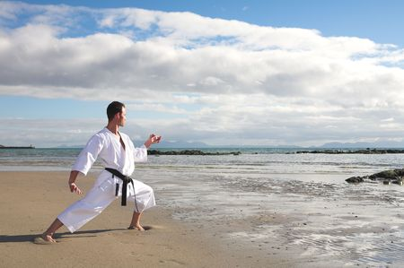 kata: Young adult man with black belt practicing a Kata on the beach on a sunny day Stock Photo