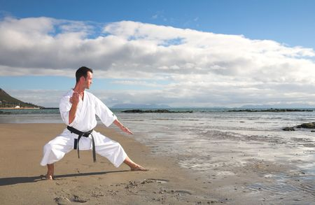 Young adult man with black belt practicing a Kata on the beach on a sunny day photo