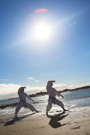 visible: Young adult man with black belt practicing a Kata on the beach on a sunny day � Lens flare visible Stock Photo