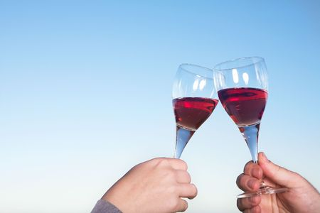 Couple toasting wineglasses against a blue sky on a summers day Stock Photo - 1092236