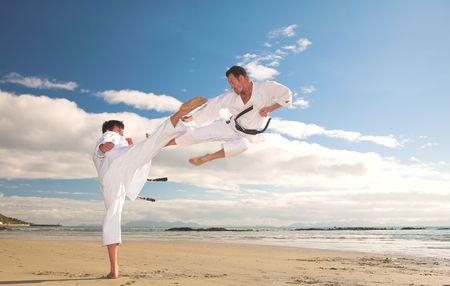 artes marciales: Los hombres adultos j�venes a practicar Karate en la playa. Una de ellas es poner en un alto y el otro que volaba por el aire (alg�n movimiento en los bordes)
