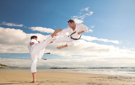 martial arts: Young adult men practicing Karate on the beach. One is in a high kick and the other flying through the air (some movement on the edges)